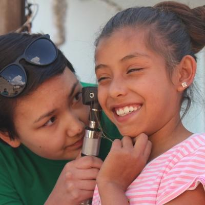 Interna de Enfermería en México realizando chequeo básico a una niña.
